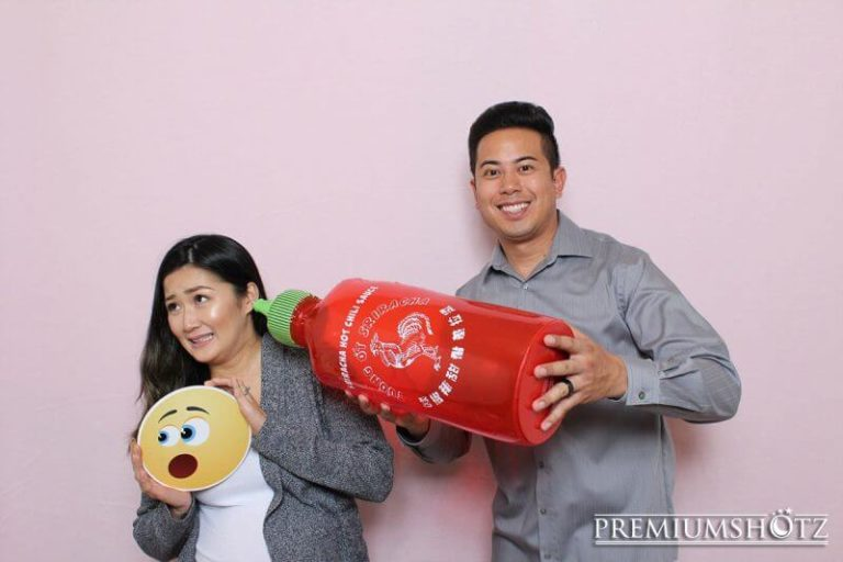 Owner and Wife posing with props in photo booth against a light pink backdrop