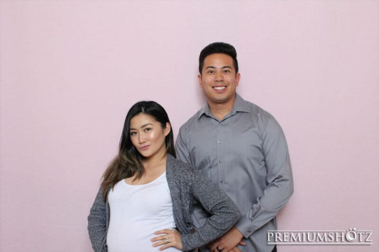 Owner and Wife smiling in photo booth against a light pink backdrop