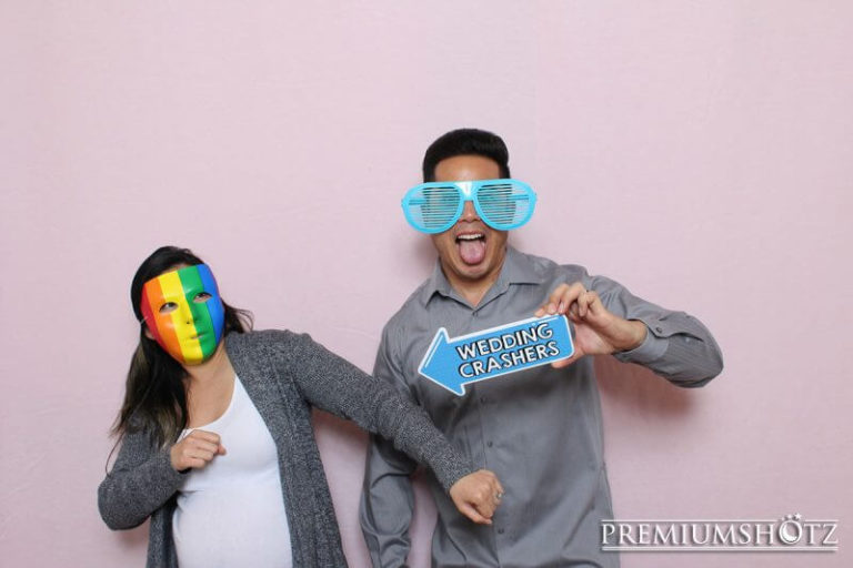 Owner and Wife posing in photo booth rental against a light pink backdrop during a recent event in San Francisco.