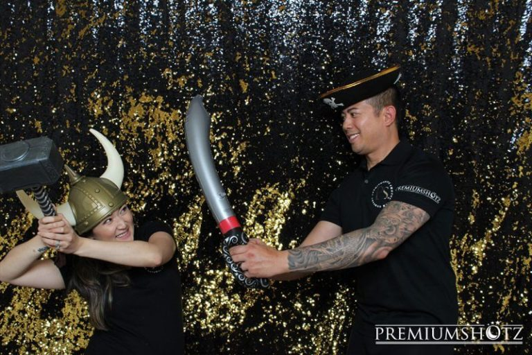 SF Photo booth rep attendants wearing polo with pirate props in front of a shiny black and gold mermaid sequin backdrop.