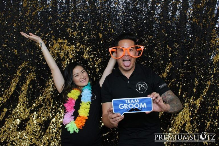 Couple holding up team groom sign and wearing lays during aloha themed corporate party, posing against a gold and black shiny sequin mermaid backdrop