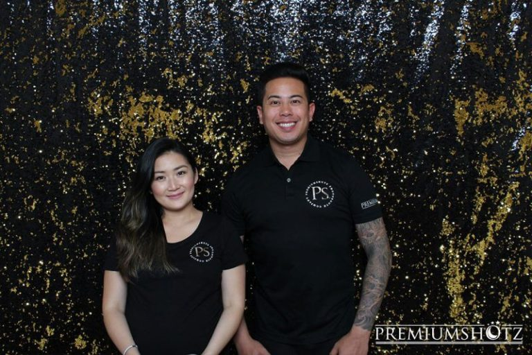 Photo booth customer service attendants wearing branded gear in front of a shiny black and gold mermaid sequin backdrop.
