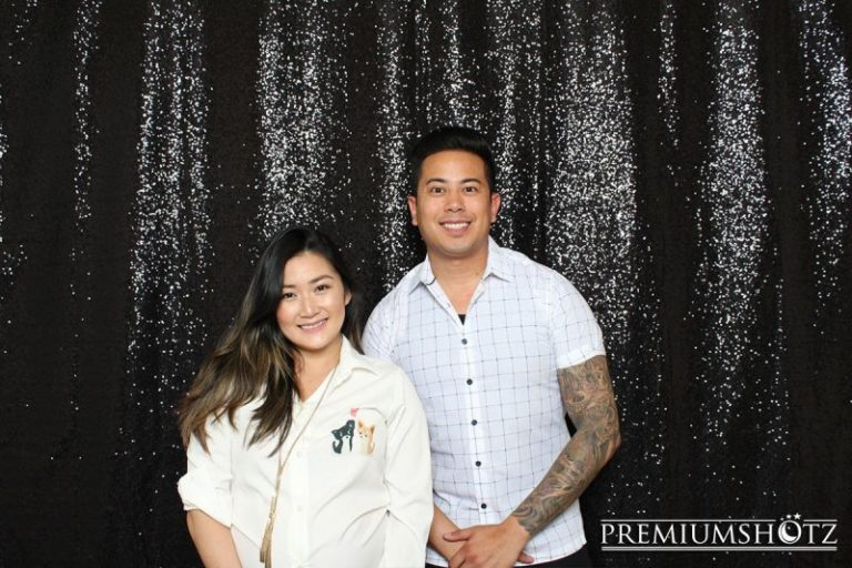 Happy wedding couple at an event in Bay Area, posing in front of a shiny black sequin backdrop.