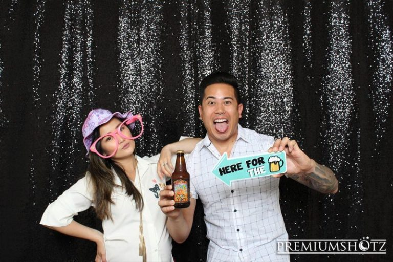 Fun couple posing in front of a shiny black sequin backdrop, holding up beer props.