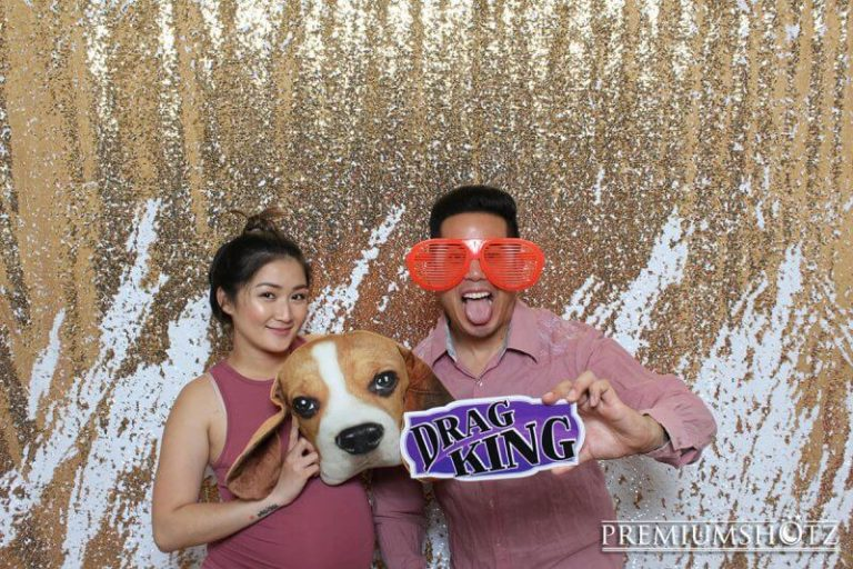 Wedding party couple in the photo booth with a dog head prop, posing against a gold and white mermaid sequin backdrop.
