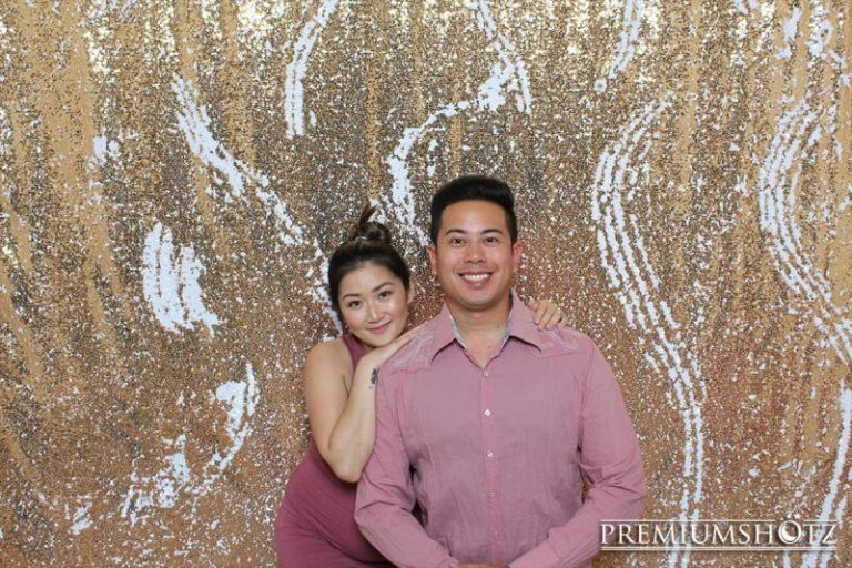 Couple smiling in the photo booth with adjustable mermaid sequin backdrop at a party.