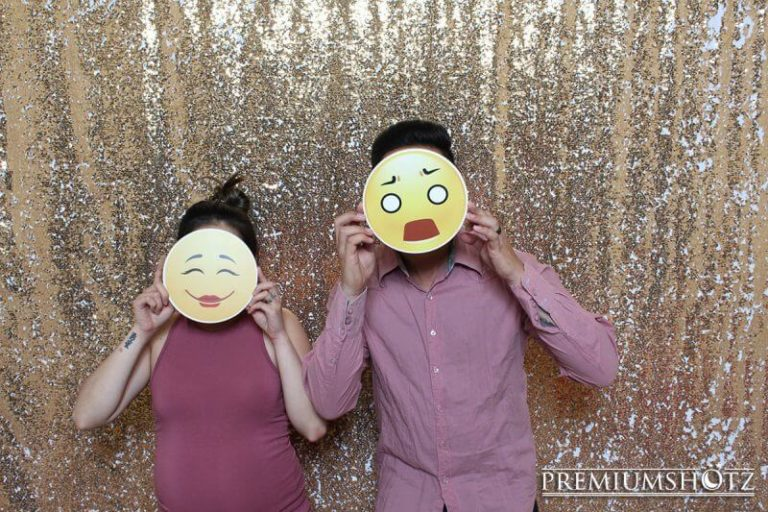 Emoji photo booth props in the photo booth rental taken against a white and gold mermaid reverse sequin backdrop