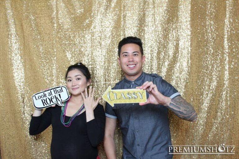 Cute married couple posing with props in the photo booth against a shiny gold sequin backdrop