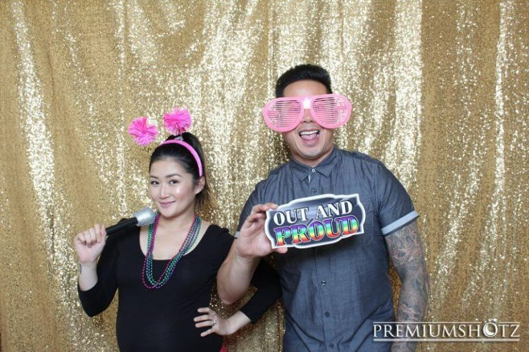 Couple posing in a photo booth rental with a gay pride prop sign, and a shiny gold sequin backdrop.