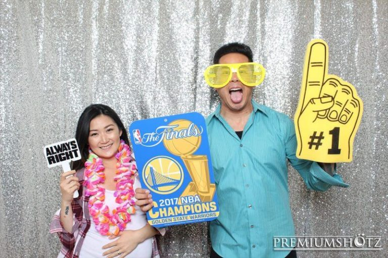 Couple having fun in the photo booth rental during the NBA Finals, with props against a shiny silver sequin backdrop.