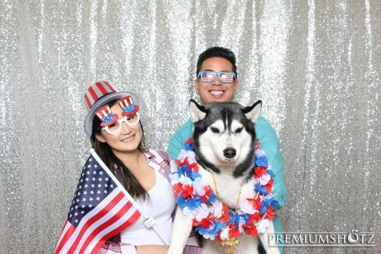 Patriotic couple with dog in photo booth with props against a shiny silver sequin backdrop.