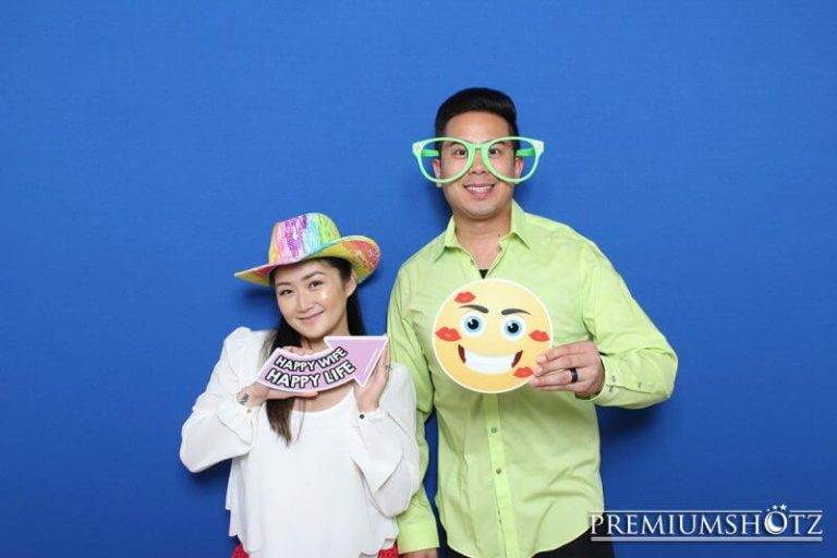 Cute couple smiling in photo booth with props against a solid blue backdrop.