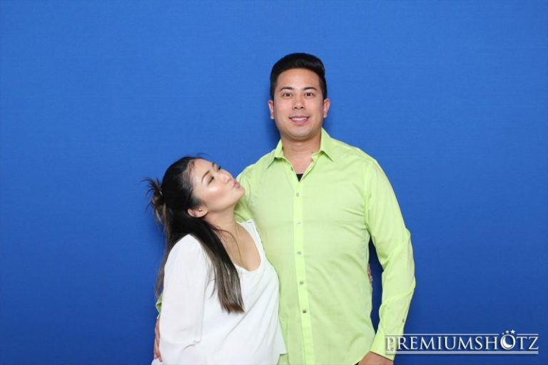 Cute couple kissing in photo booth rental with props against a solid blue backdrop in San Francisco.