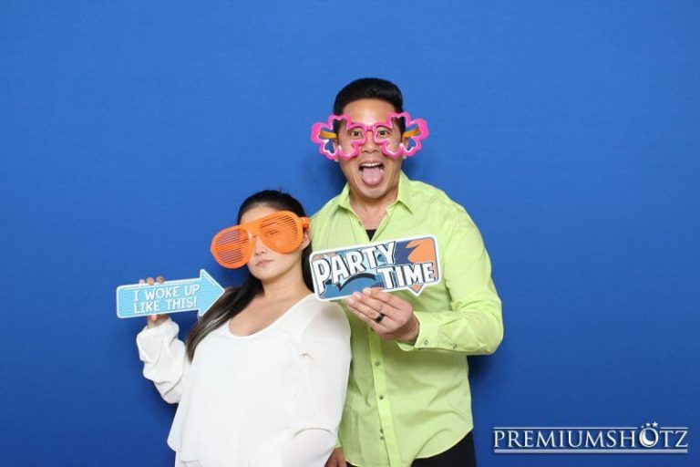 Cute couple posing in photo booth with props against a solid blue backdrop.