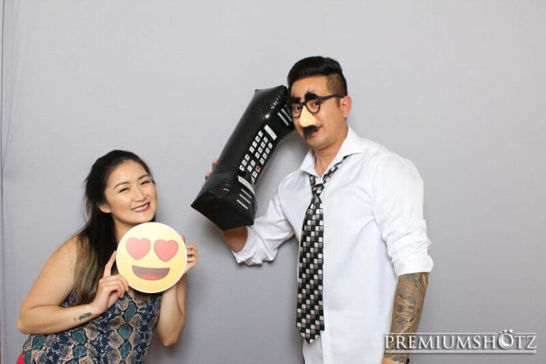 Couple posing in photo booth against a solid gray backdrop