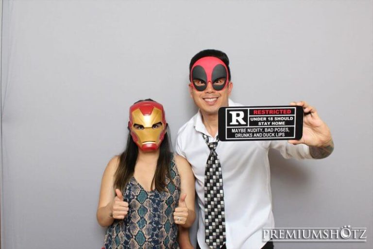 Cute couple posing in photo booth rental with props against a solid gray backdrop.