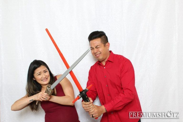Owner and Wife play fighting in photo booth with a white sequin background