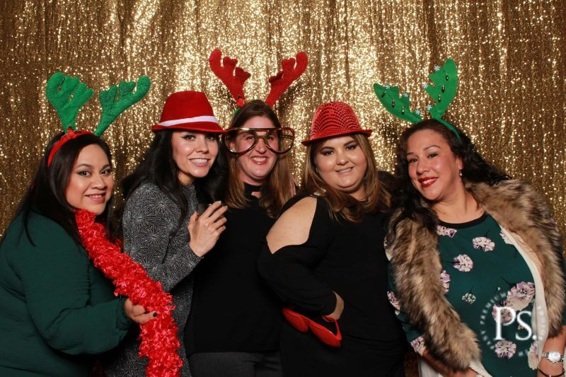 Group of women posing in a christmas photo booth