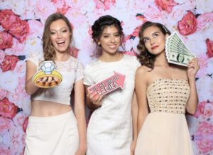 Women posing in the photo booth on a flower backdrop